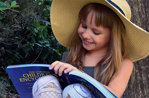 """Aveline (5) soaks up the Orlando, Florida weather as she reads and re-reads her favorite history and science topics from Level A's Usborne Children's Encyclopedia. Aveline is moving on to Level B soon."" -The M family, Orlando, FL"