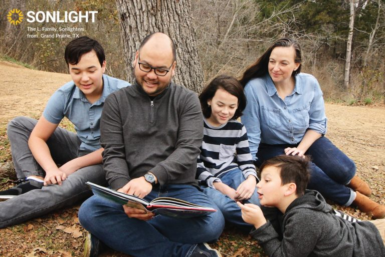 an entire family reads outside