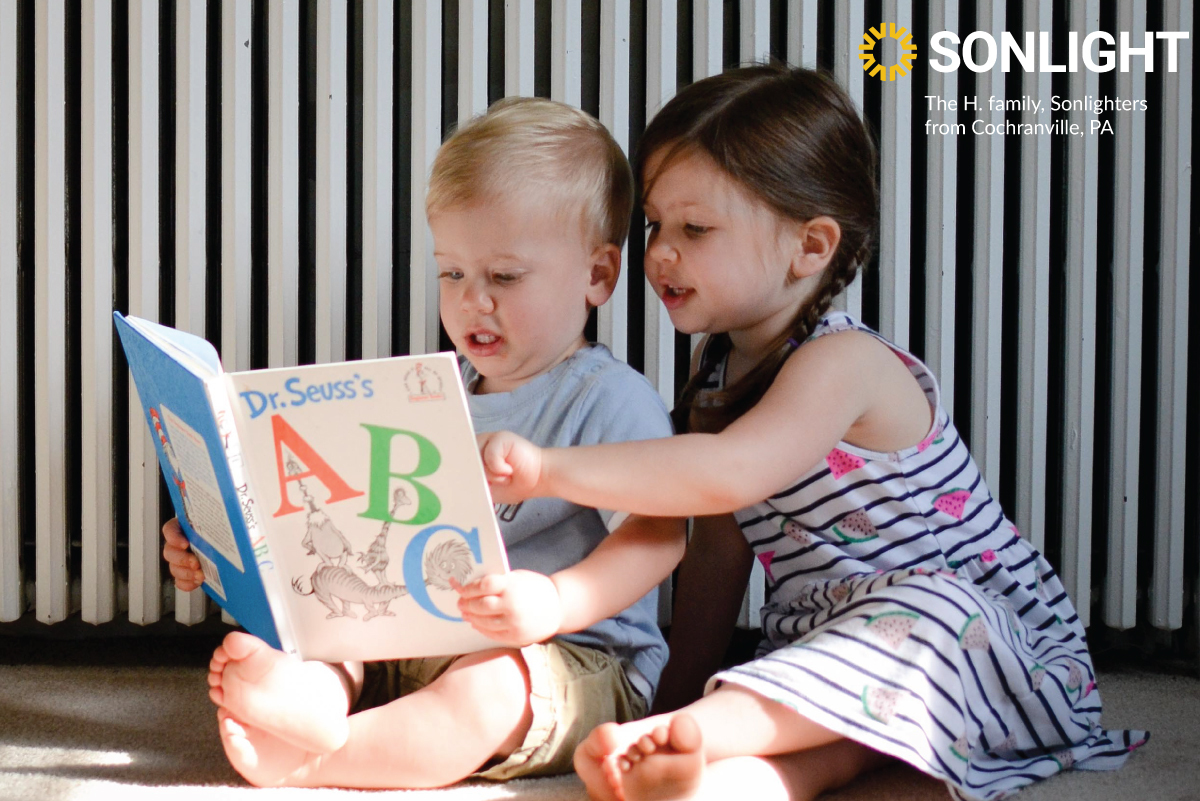 two preschoolers enjoy a book