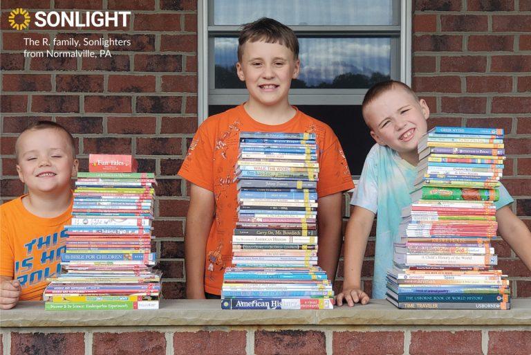 three children pose behind brick wall with Sonlight stacks