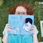 high school senior poses with favorite books